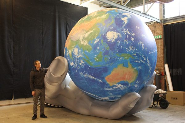 2.5m printed globe with silver hand in studio