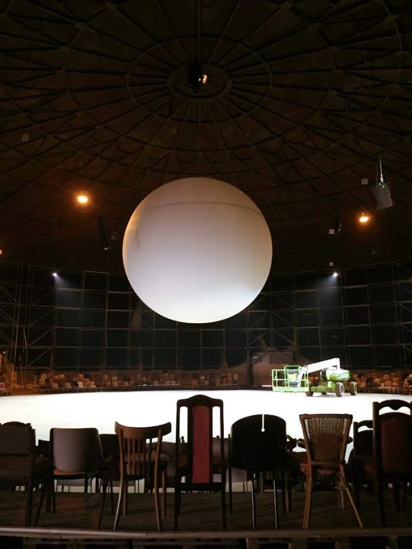 single white ball on stage with empty chairs